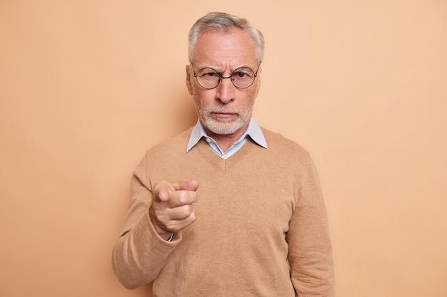 Ernster strenger bärtiger älterer mann zeigt mit dem zeigefinger