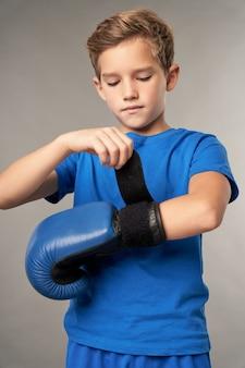 Ernster süßer junge, der hände für das boxtraining vorbereitet, während er vor grauem hintergrund steht
