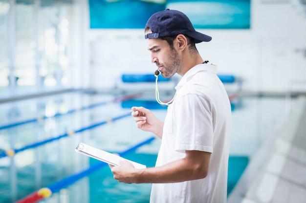 Ernster trainer, der klemmbrett hält und pfeife am pool durchbrennt
