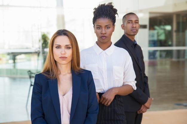 Ernster überzeugter weiblicher unternehmensleiter, der im büro aufwirft