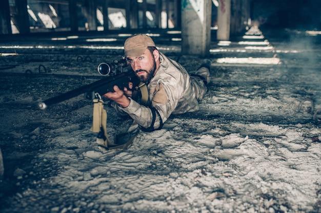 Ernster und berufsmann liegt aus den grund und schaut durch linse. er zielt. kerl trägt militärkleidung. er wartet.