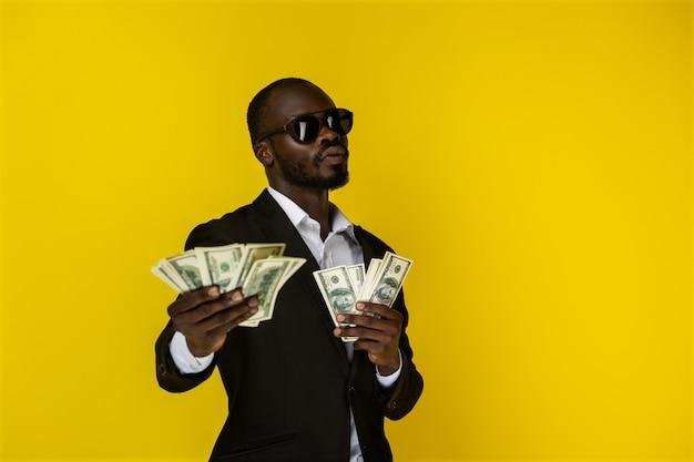 Ernster und cooler mann zeigt das geld