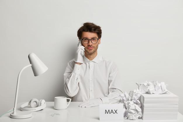 Ernster unrasierter hipster-typ mit stilvoller frisur hat smartphone-konversation