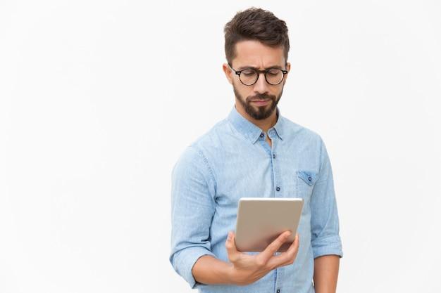 Ernster unternehmer, der e-mail auf tablette überprüft