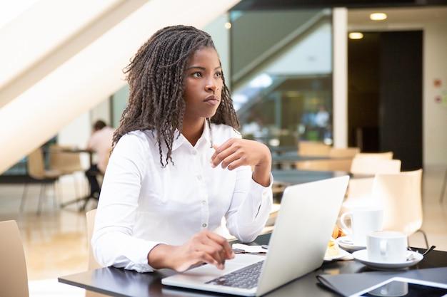Ernster weiblicher büroangestellter, der computer verwendet