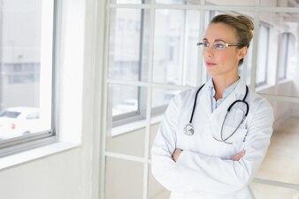 Ernster weiblicher doktor mit den armen kreuzte im krankenhaus
