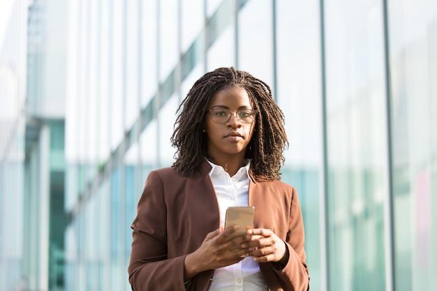 Ernster weiblicher geschäftsfachmann, der smartphone hält