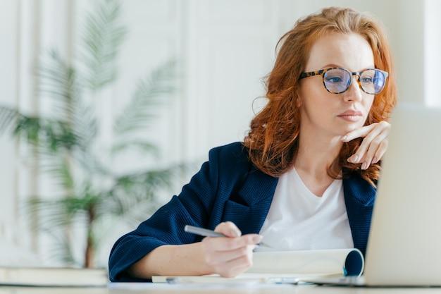 Ernster weiblicher trainer macht aufzeichnungen im notizblock