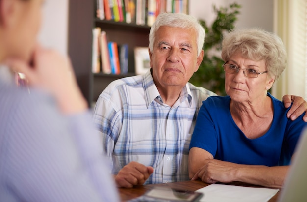 Ernstes älteres paar, das im büro sitzt