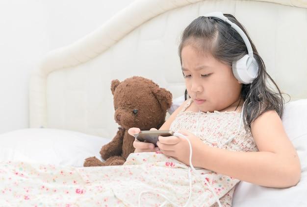 Ernstes asiatisches mädchen, das am intelligenten telefon spielt