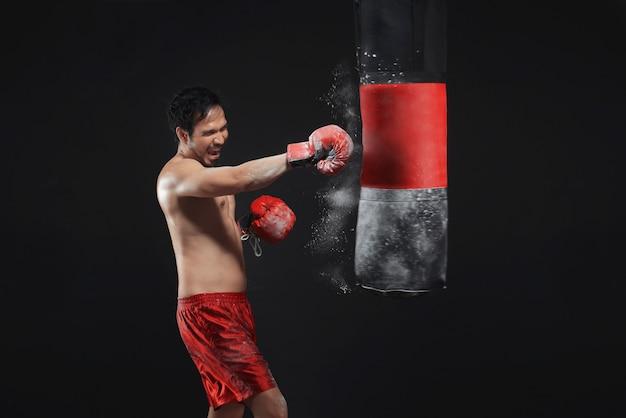 Ernstes asiatisches männliches boxertraining mit dem lochen des sandsacks