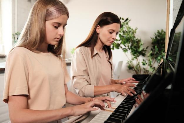 Ernstes blondes junges mädchen, das tasten des klaviers während des trainings während der musikstunde zu hause mit ihrer mutter drückt, die in der nähe sitzt