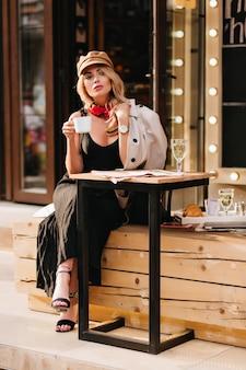 Ernstes blondes mädchen in den schwarzen schuhen, die im straßencafé chillen und tee genießen. attraktive junge frau trägt stilvolle sandalen und braunen hut, der weg schaut und tasse kaffee hält.
