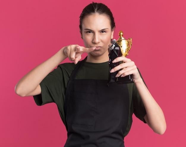 Ernstes junges brünettes friseurmädchen in uniform, das haarschneidemaschinen und siegerpokal hält und auf die kamera zeigt