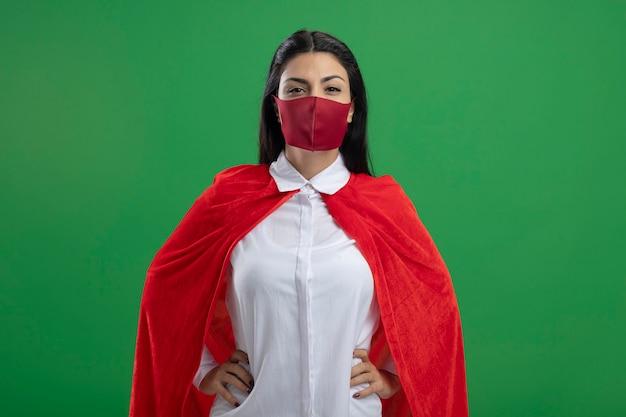 Ernstes junges kaukasisches superheldenmädchen, das maske hält, die hände auf ihren hüften betrachtet kamera mit ernstem blick lokalisiert auf grünem hintergrund mit kopienraum