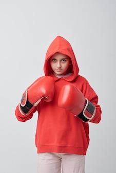 Ernstes junges mädchen im kapuzenpulli, das mit wut schaut und bereit für das boxen ist