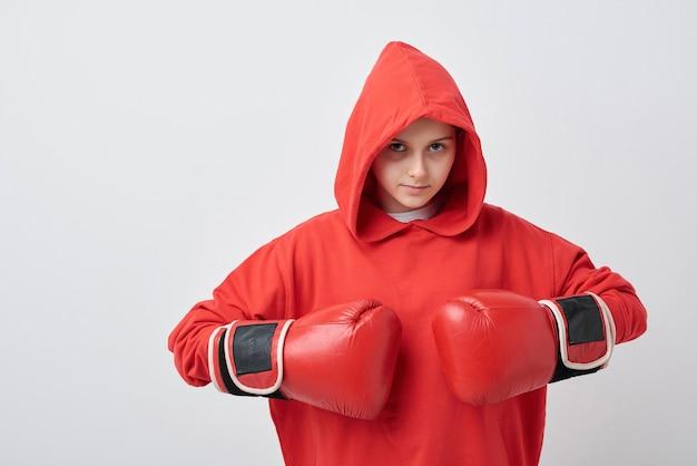 Ernstes junges mädchen im roten kapuzenpulli und in den boxhandschuhen, die hände an ihrer brust halten, bereit, rivalen anzugreifen, während sie vor der kamera stehen