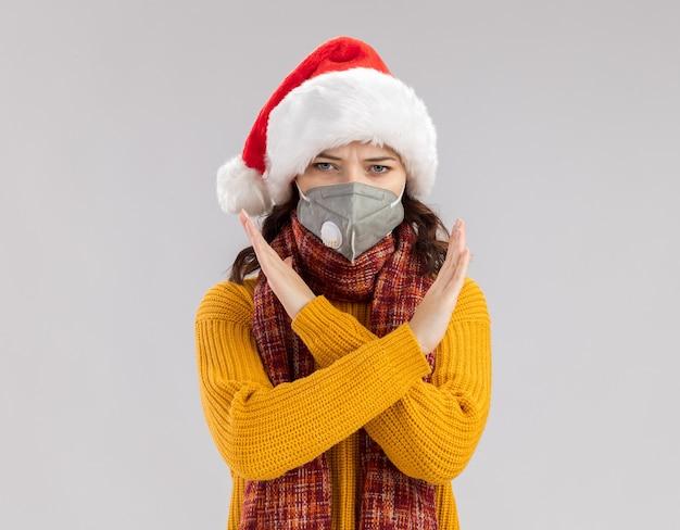 Ernstes junges slawisches mädchen mit weihnachtsmütze und mit schal um hals, der medizinische maske trägt, die hände kreuzt, die kein zeichen gestikulieren