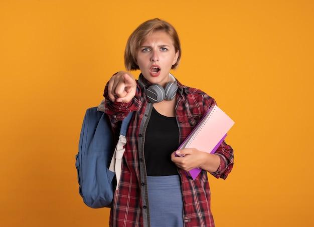 Ernstes junges slawisches studentenmädchen mit kopfhörern, das rucksack trägt, hält buch- und notizbuchpunkte an der kamera
