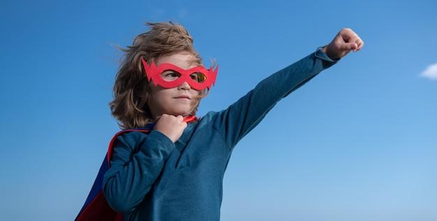 Ernstes kind, das ein superheldenkostüm trägt. superheldenkind gegen blauen sommerhimmelhintergrund. kind, das spaß im freien hat. kinder-power-konzept.