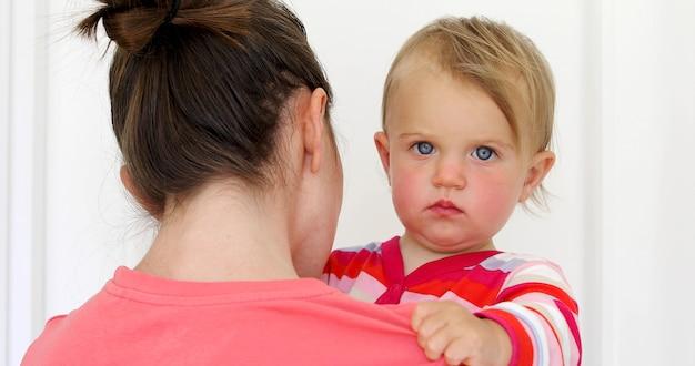 Ernstes kind mit rotem frechem in den händen der mutter