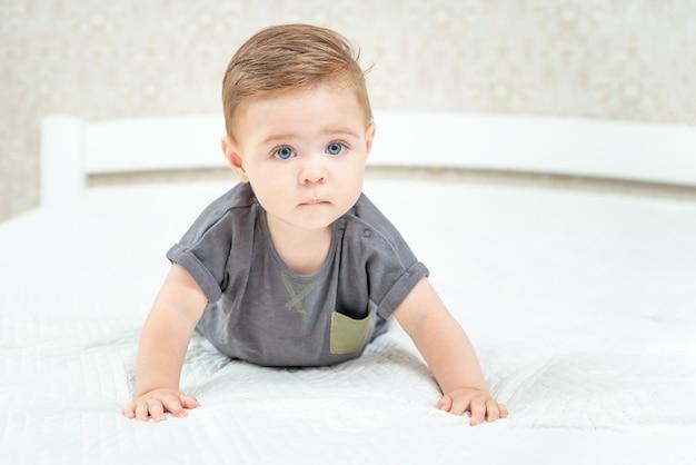 Ernstes kleines baby, das auf dem bett auf einem weißen laken im schlafzimmer der eltern krabbelt, das in die kamera schaut