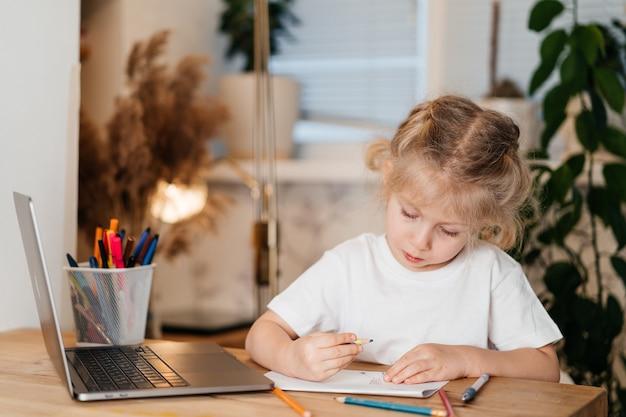 Ernstes kleines mädchen, das über ihren laptop lacht und hausaufgaben in einem notizbuch, hauptlernkonzept macht