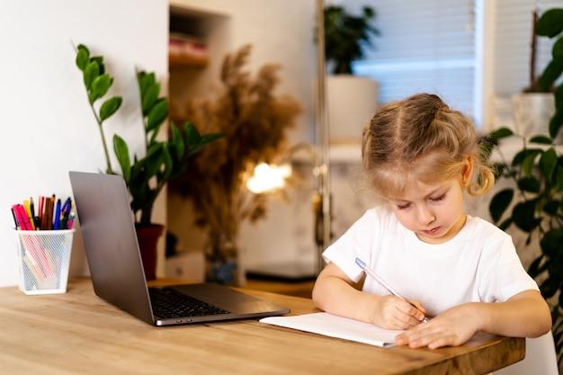 Ernstes kleines mädchen, das über ihren laptop lacht und hausaufgaben in einem notizbuch macht.