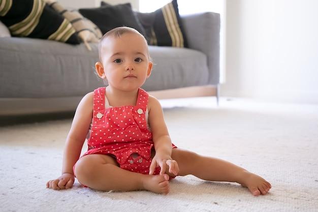 Ernstes kleines mädchen in roten latzhosen, die zu hause auf teppich sitzen. schönes nachdenkliches barfußes kleinkind, das allein im wohnzimmer sitzt kindheit, wochenende, zu hause konzept