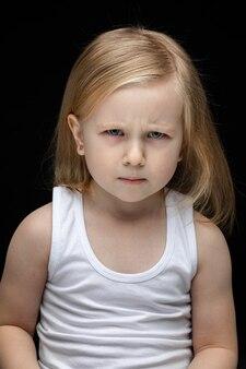 Ernstes kleinkindmädchen runzelt die stirn und schaut in die kamera, während es auf schwarz sitzt