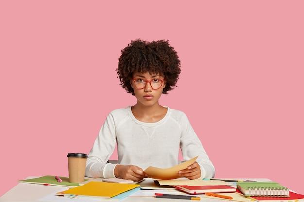 Ernstes konzentriertes studentenmädchen, das am schreibtisch gegen die rosa wand aufwirft