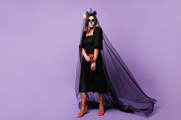 Ernstes mädchen, das als schwarze witwe an halloween aufwirft. foto des modells, das blumenkrone trägt und rose hält.