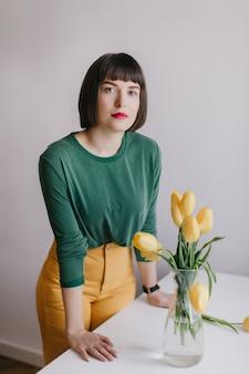 Ernstes mädchen mit trendigem make-up, das nahe tisch mit blumen auf ihm steht. interessiertes weißes weibliches modell, das neben gelben tulpen aufwirft.