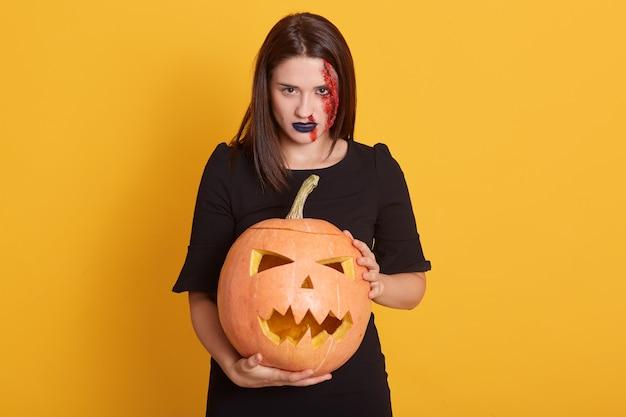 Ernstes mädchen mit wütendem gesichtsausdruck stehend mit kürbis in den händen im studio lokalisiert auf gelber, attraktiver frau mit blutiger wunde auf ihrem gesicht, halloween-konzept.