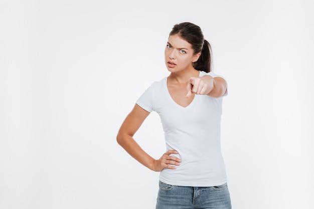 Ernstes modell im t-shirt, das an der vorderen isolierten weißen wand zeigt