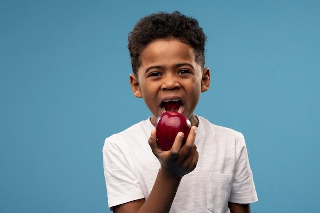 Ernstes oder beleidigtes süßes kleines boyin weißes t-shirt, das seine arme auf der brust verschränkt, während es vor kamera über blau steht
