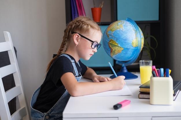Ernstes rothaariges mädchen in brillen, das zu hause studiert, hausaufgaben machen. schreiben. streber. zurück zur schule