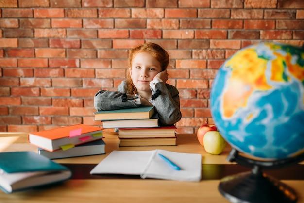 Ernstes schulmädchen mit lehrbüchern posiert am tisch.