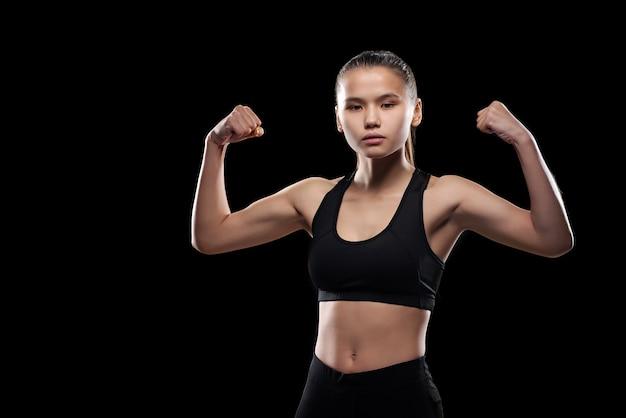 Ernstes sportliches mädchen in schwarzer aktivkleidung, das isoliert steht, während es ihre körperliche stärke zeigt