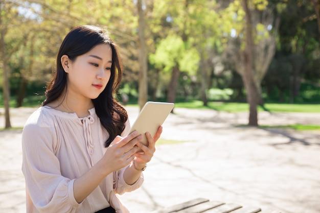 Ernstes studentenmädchen, das artikel für klassenprojekt studiert