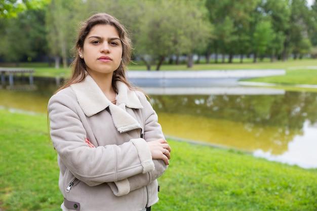 Ernstes studentenmädchen, das im park nahe teich aufwirft