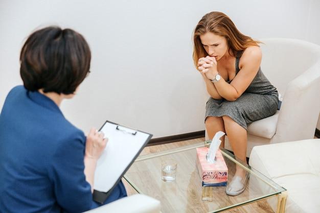 Ernstes und durchdachtes mädchen sitzt auf sofa und schaut unten. sie hält die hand nah an den mund. sie denkt. der therapeut schreibt informationen auf papier.