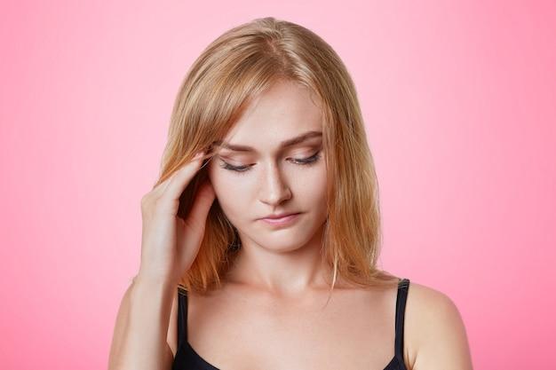 Ernsthaft angenehm aussehendes junges weibliches model hält die hand an den schläfen, schaut nachdenklich nach unten, hat nachdenklichen ausdruck, versucht sich an etwas zu erinnern, hat nach einem langen arbeitstag kopfschmerzen, ruht zu hause
