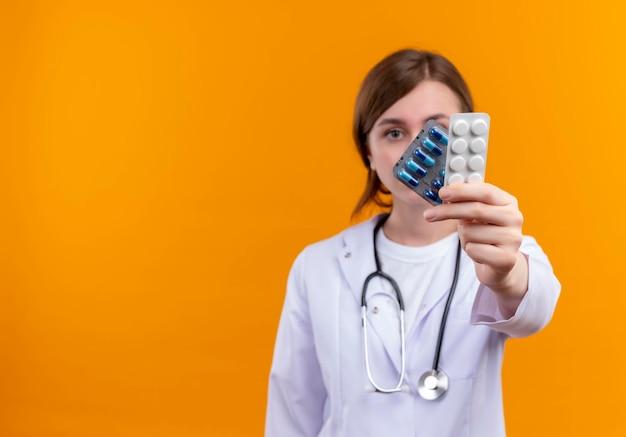 Ernsthaft aussehende junge ärztin, die medizinische robe und stethoskop trägt, die medizinische drogen auf isoliertem orange raum mit kopienraum strecken