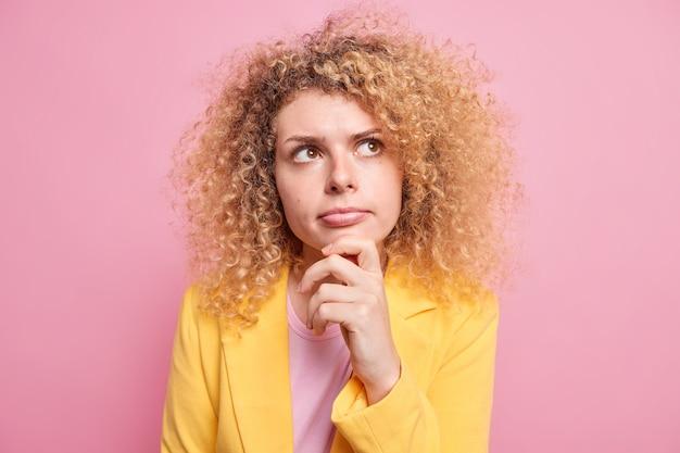 Ernsthaft aussehende junge frau mit lockigem haar hält kinn schaut nach oben und denkt tief konzentriert auf etwas, das über verdachtssituationen nachdenkt, gekleidet in formaler gelber jacke, isoliert über rosafarbener wand