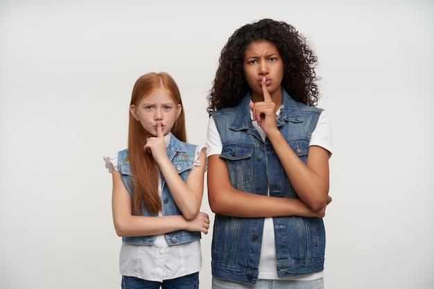 Ernsthaft aussehende junge langhaarige damen, die die augenbrauen runzelten und in stiller geste die zeigefinger hoben, um schweigen zu bitten, freizeitkleidung trugen und auf weiß posierten