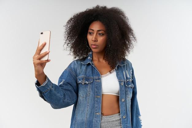 Ernsthaft aussehende junge lockige dunkelhäutige dame posiert über weißer wand in freizeitkleidung, hält smartphone in erhobener hand und macht ein foto von sich selbst making