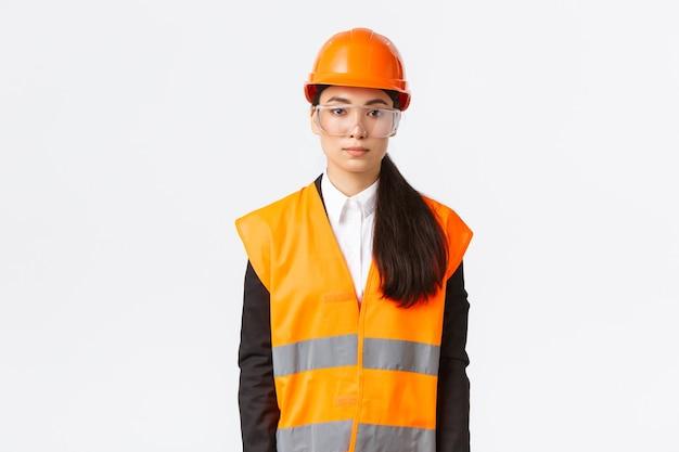 Ernsthaft aussehende professionelle asiatische bauingenieurin, architektin im baubereich mit uniform, schutzhelm über business-anzug, stehender weißer hintergrund, unternehmen inspizieren