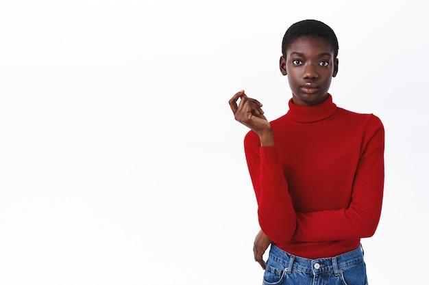 Ernsthaft aussehende, selbstbewusste afroamerikanische unternehmerin mit kurzem haarschnitt, der frech und edel aussieht