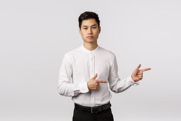 Ernsthaft aussehender frecher und hübscher asiatischer tausendjähriger kerl in der formellen kleidung, im hemd und in den hosen, nach rechts zeigend, durchsetzungsfähig schauend, arbeitgeber geben richtung, bieten produkt an